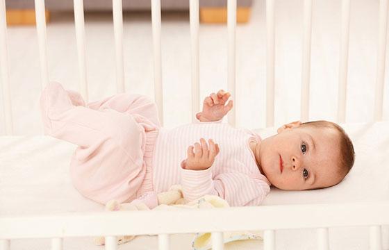 Baby girl in white crib mattress