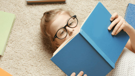 Girl with spectacles reading book