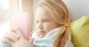 Young Girl Playing With Pink Mobile Phone