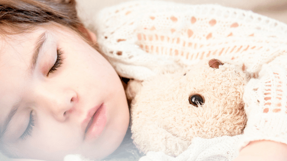 Young girl sleeping with teddy