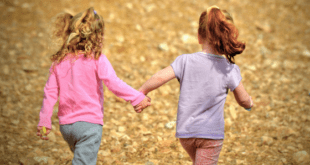 Two girls running holding hands
