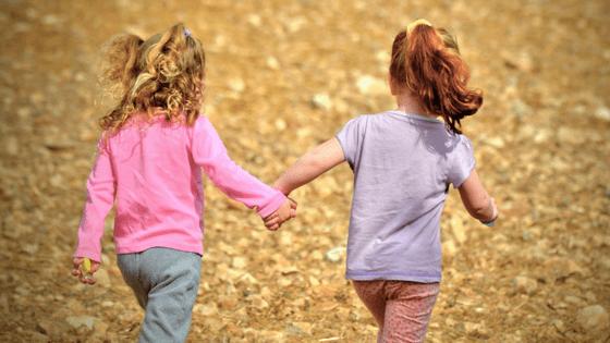 Two girls running holding hands