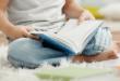 Boy reading book sitting on carpet