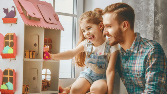 Girl and dad playing with doll house