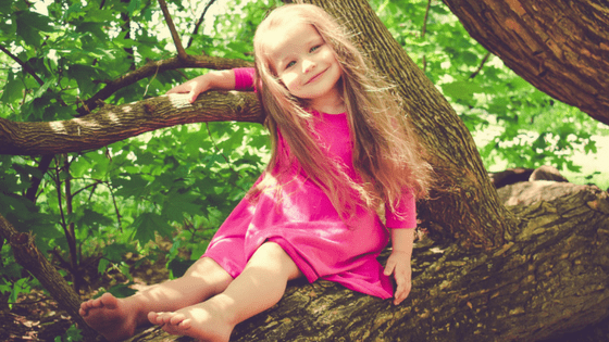 Girl in pink dress climbing tree