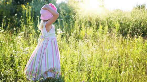 Girl in pink hat playing outside