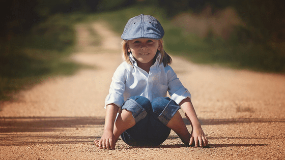 Happy Child Sitting On Road