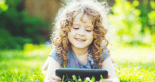 Kid playing with tablet lying on grass