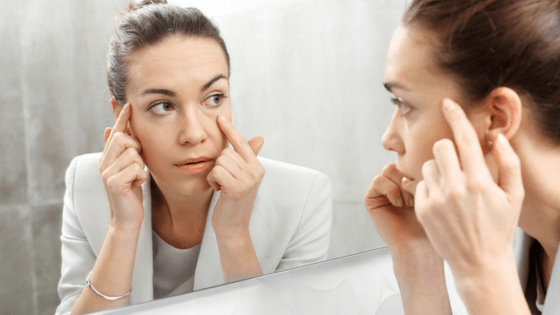 Woman looking for wrinkles in mirror