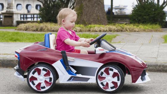Blonde toddler riding car