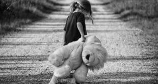 Child walking with stuffed lion