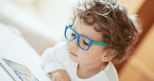 Kid with blue glasses playing with tablet