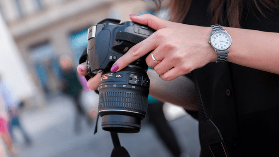 womans hands on professional camera