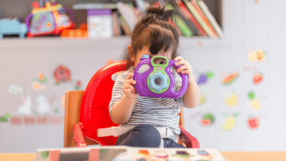 Little Girl Playing With Purple Toy