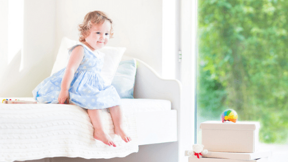 Toddler girl sitting on bed