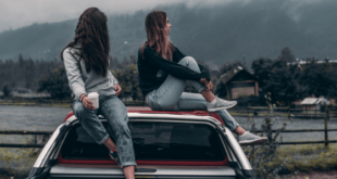Girls sitting on car