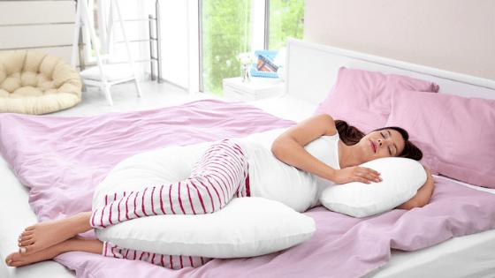 Pregnant woman sleeping on pink duvet