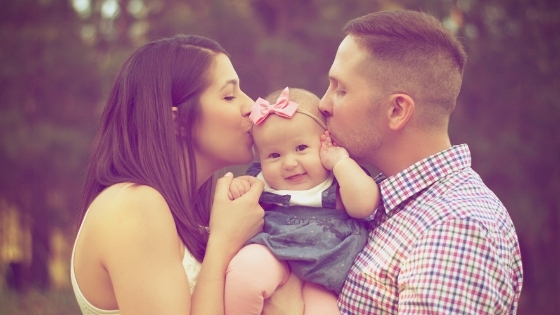 Parents kissing baby girl
