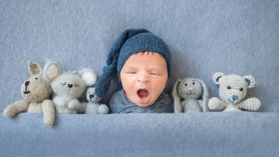 Newborn boy in bed with toys