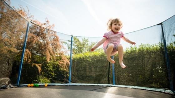 Toddler Girl Jumping on big trampoline