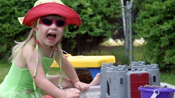 Girl playing outside wearing sun hat