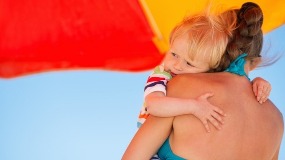 Mom holding baby under umbrella