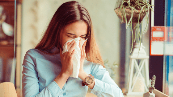 Woman with allergies blowing nose