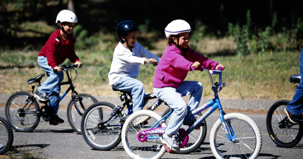 Kids riding bikes on road - summer safety tips for parents
