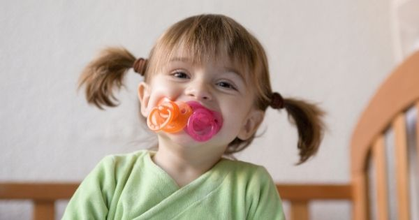 Baby girl with two pacifiers