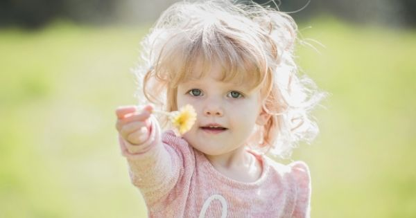 Child holding out flower